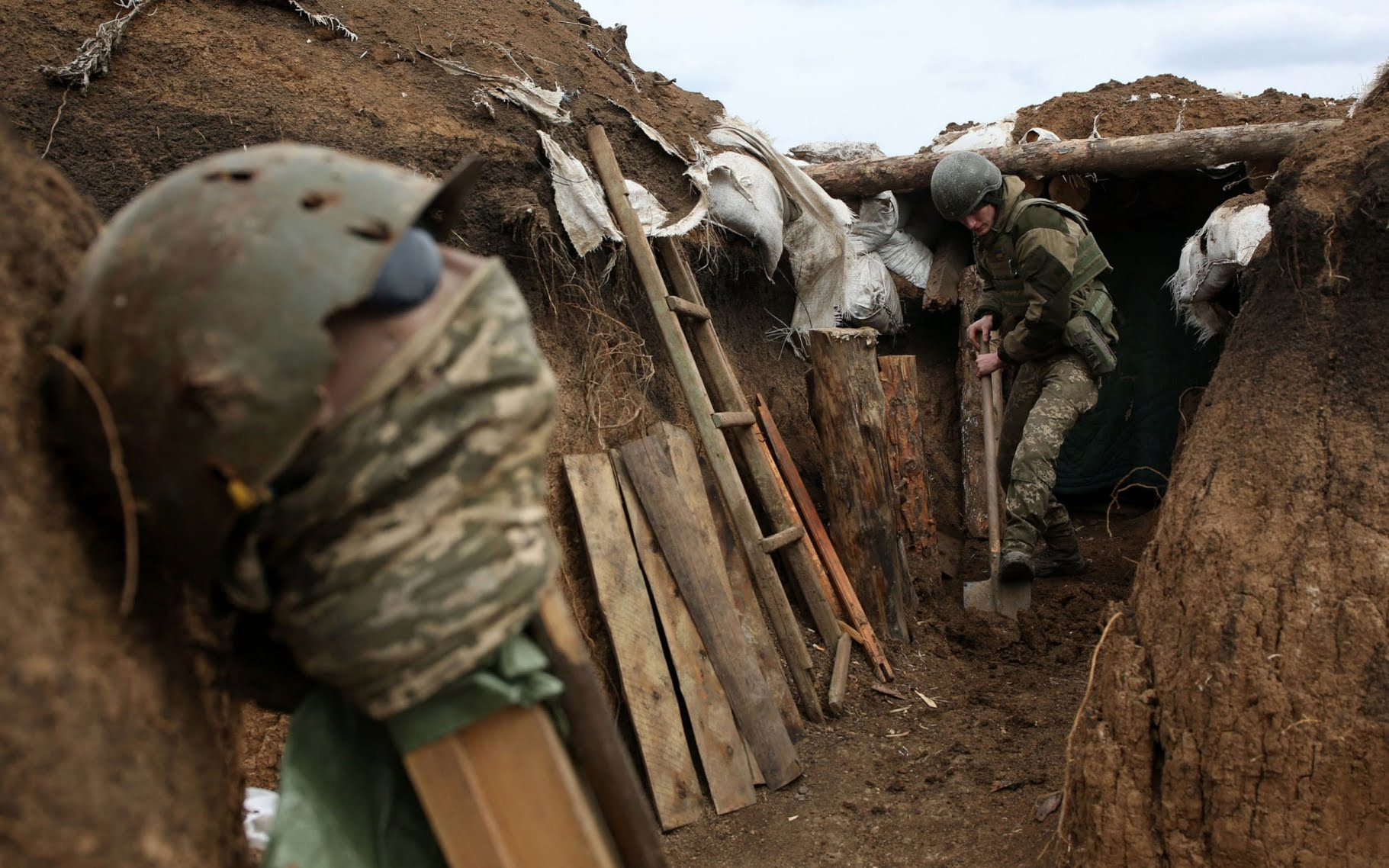 An Ukrainian serviceman digs the ground of a trench as he stands at his post on the frontline on April 8